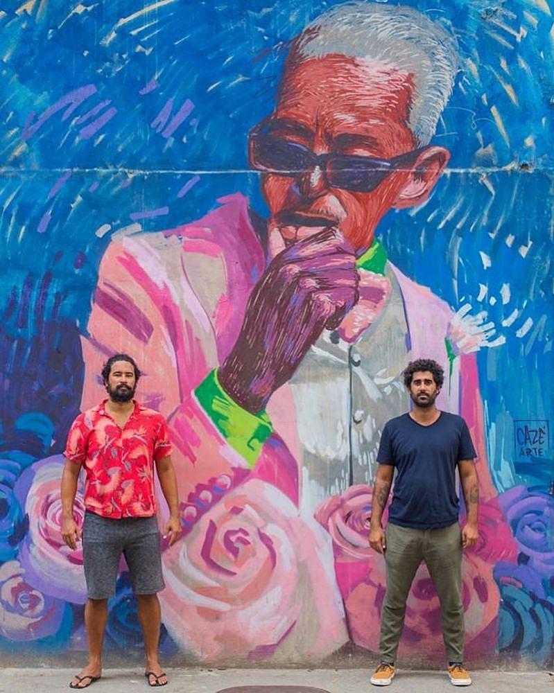 Pedro e Cazé em frente ao grafite do músico Cartola