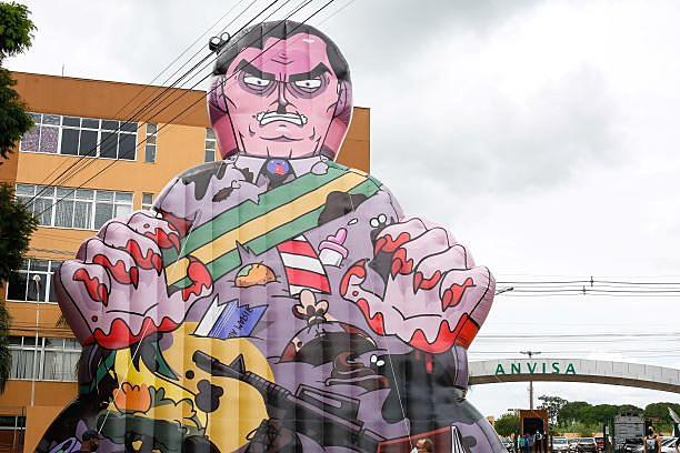 Manifestantes erguem um boneco inflável do presidente Jair Bolsonaro em frente à sede da Anvisa no domingo (17), dia em que a agência decidiu sobre o uso emergencial de vacinas contra covid: movimentos pelo impeachment começam a ir para as ruas
