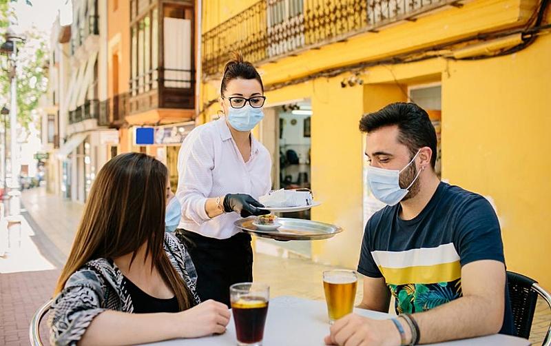 casal no bar de máscara