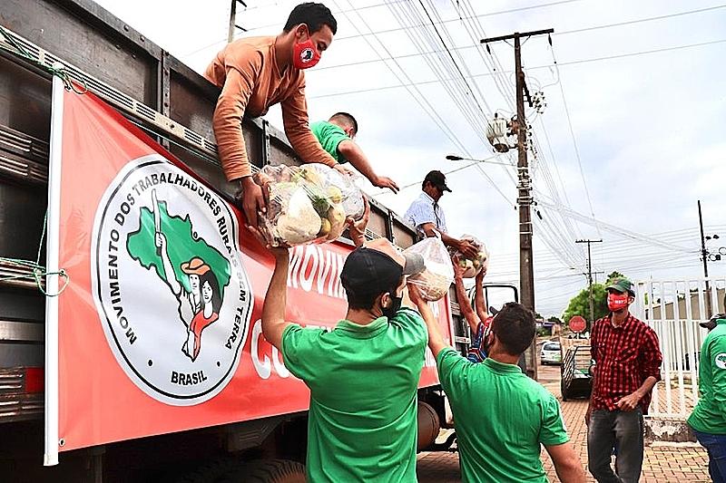 Famílias descarregam um caminhão com alimentos